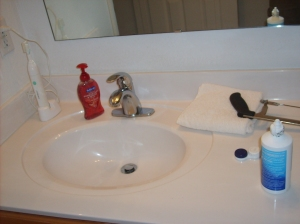 All the bathroom essentials.  Hand soap, tooth brush, contact solution, hack saw.